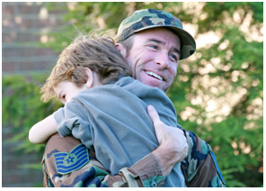 military man embrassing a child